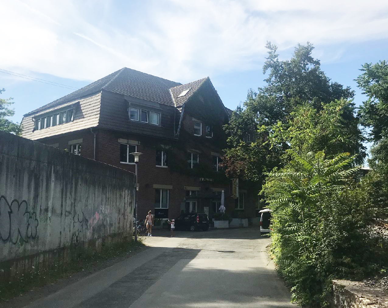 Zufahrt zum Büro: links Betonwand, rechts Bäume, am Ende dreigeschossiger Bau, Zugang frontal